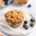 bakery style blueberry muffin on a plate with blueberries