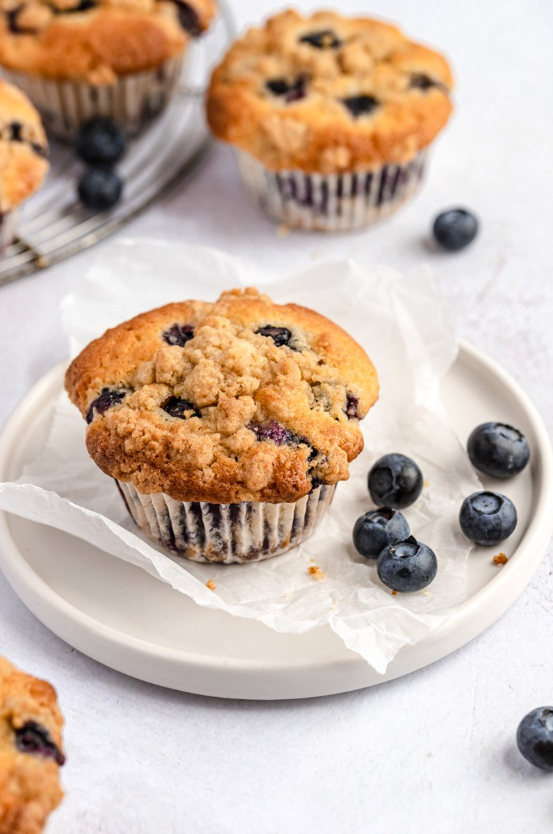 easy bakery style blueberry muffin on a plate with blueberries