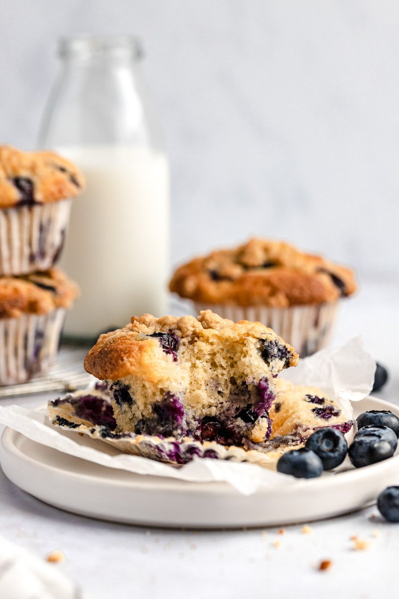 bakery style blueberry muffin on a plate with a bite taken out