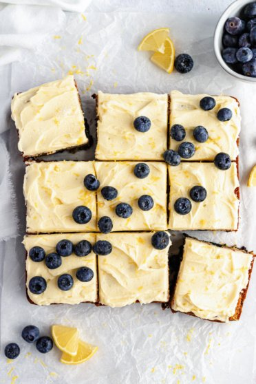 healthy lemon blueberry zucchini cake cut into nine slices topped with frosting
