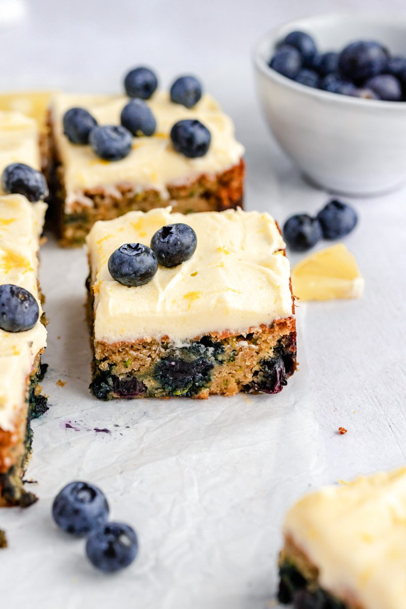 piece of blueberry zucchini cake next to blueberries