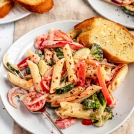 creamy vegan pasta primavera on a plate with garlic bread