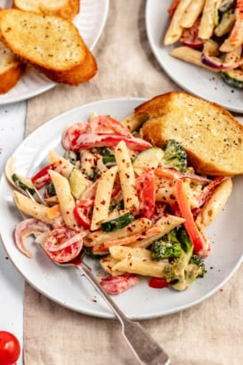 creamy vegan pasta primavera on a plate with garlic bread