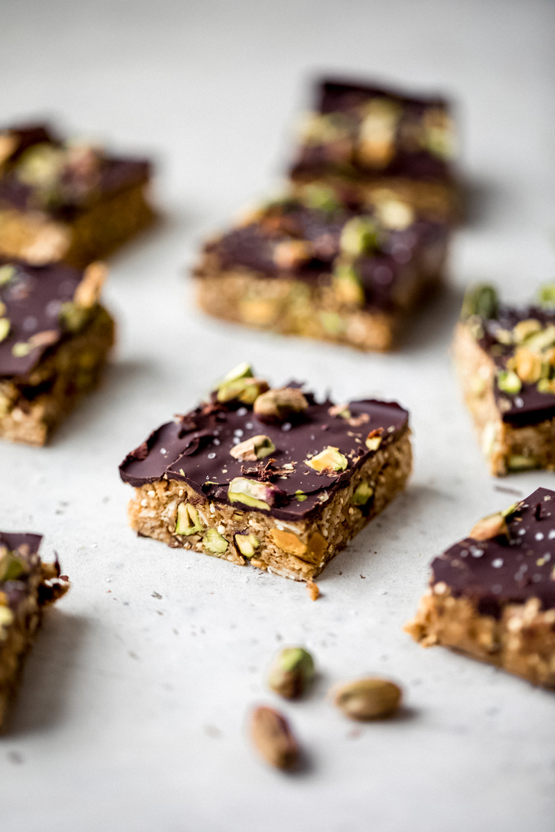 quinoa granola bar with dark chocolate on a grey surface with pistachios
