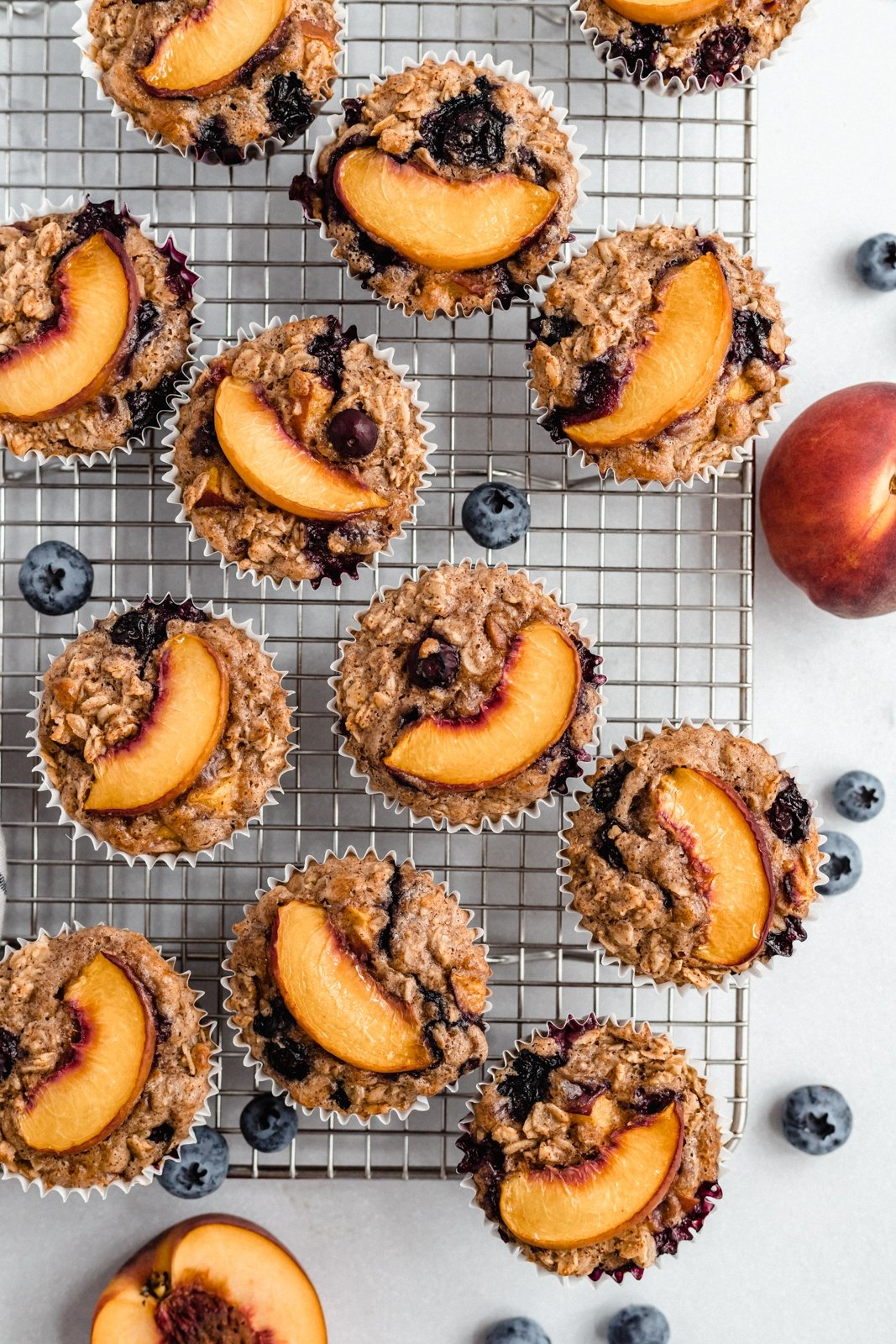 blueberry baked oatmeal cups topped with peach slices on a wire rack