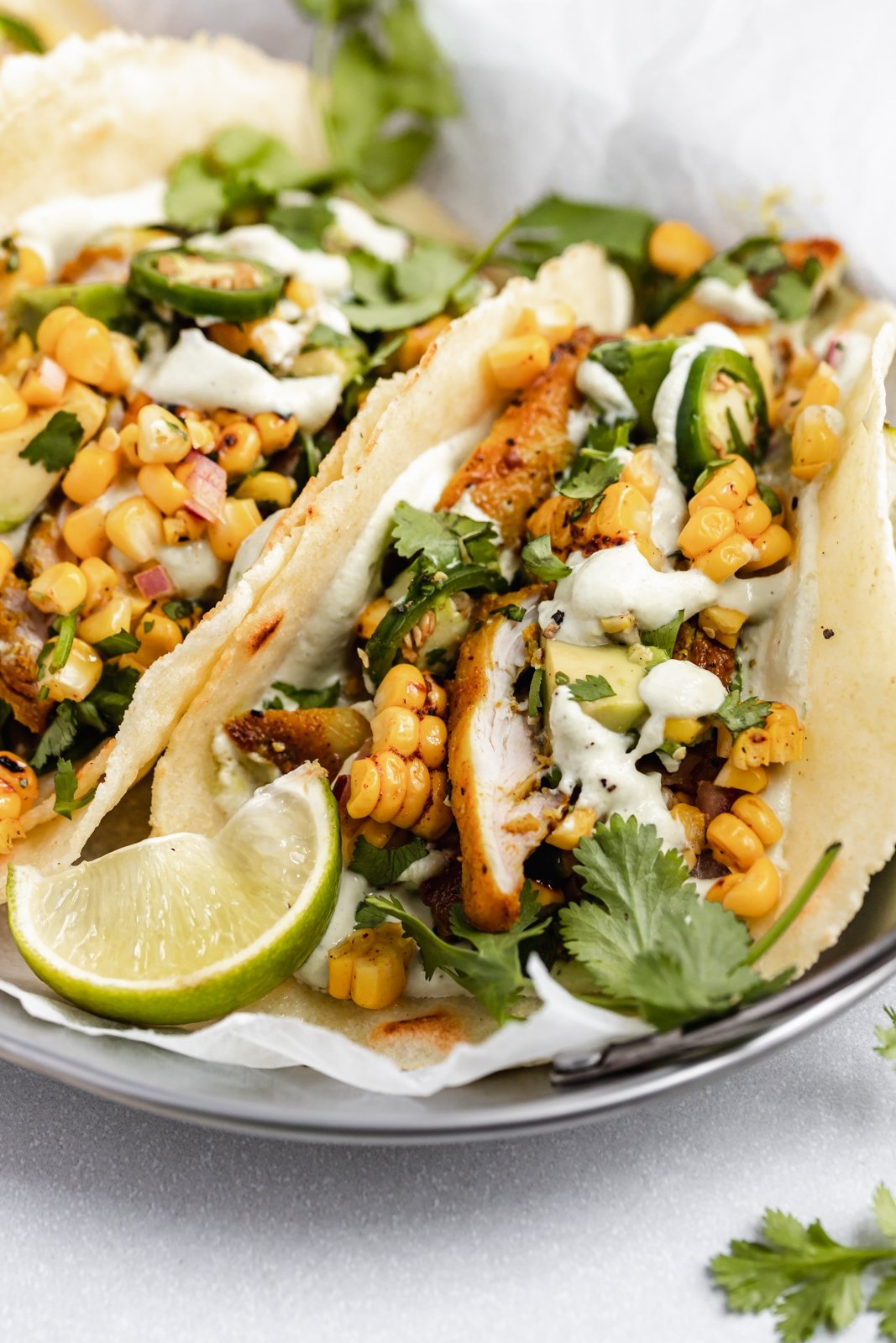 up close photo of street corn chicken tacos in a basket