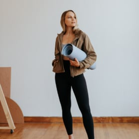 woman in fitness clothes with a yoga mat