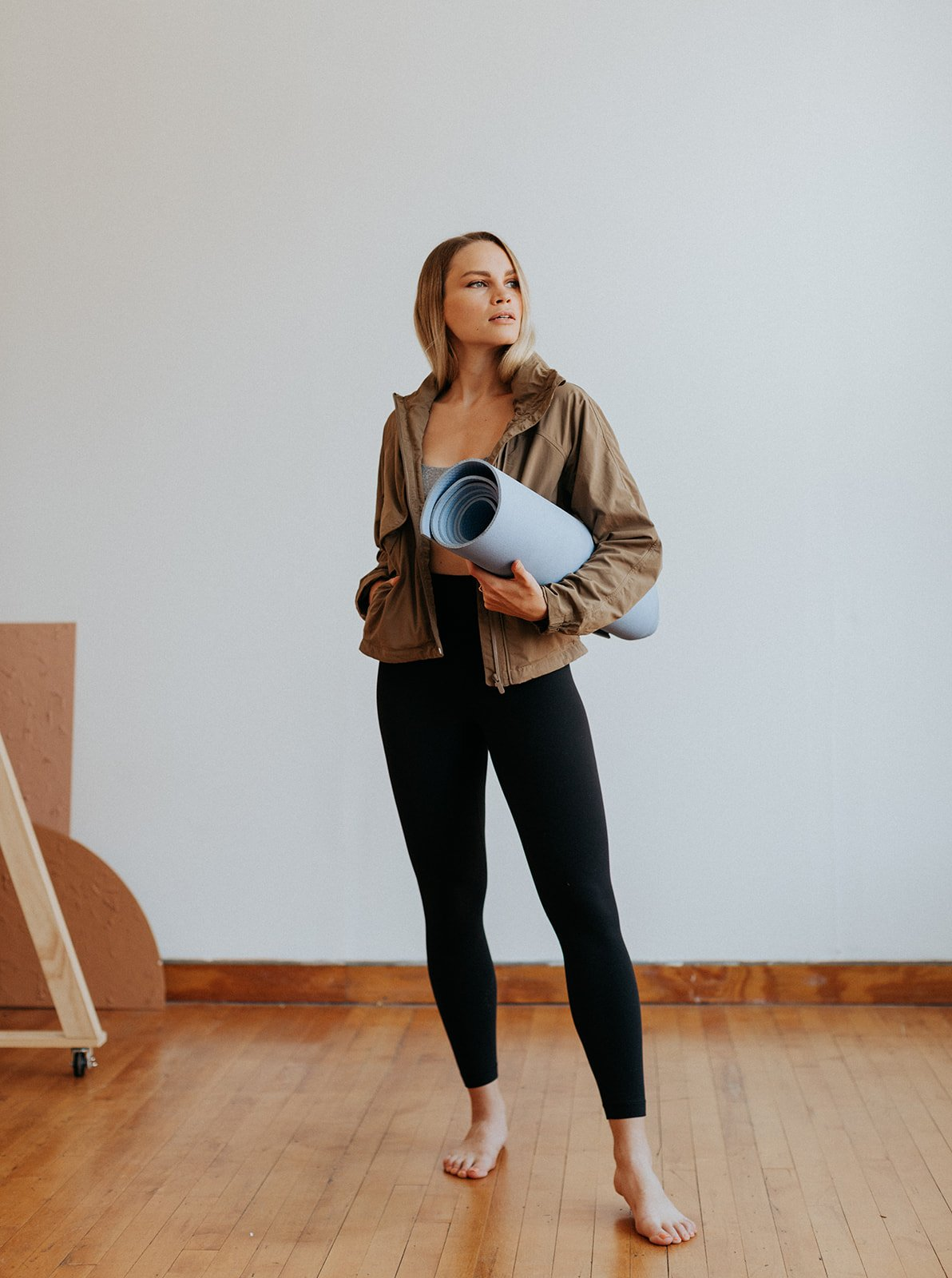 woman in a jacket and leggings holding a yoga mat
