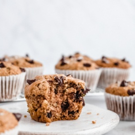 healthy chocolate chip zucchini muffin on a plate with a bite taken out