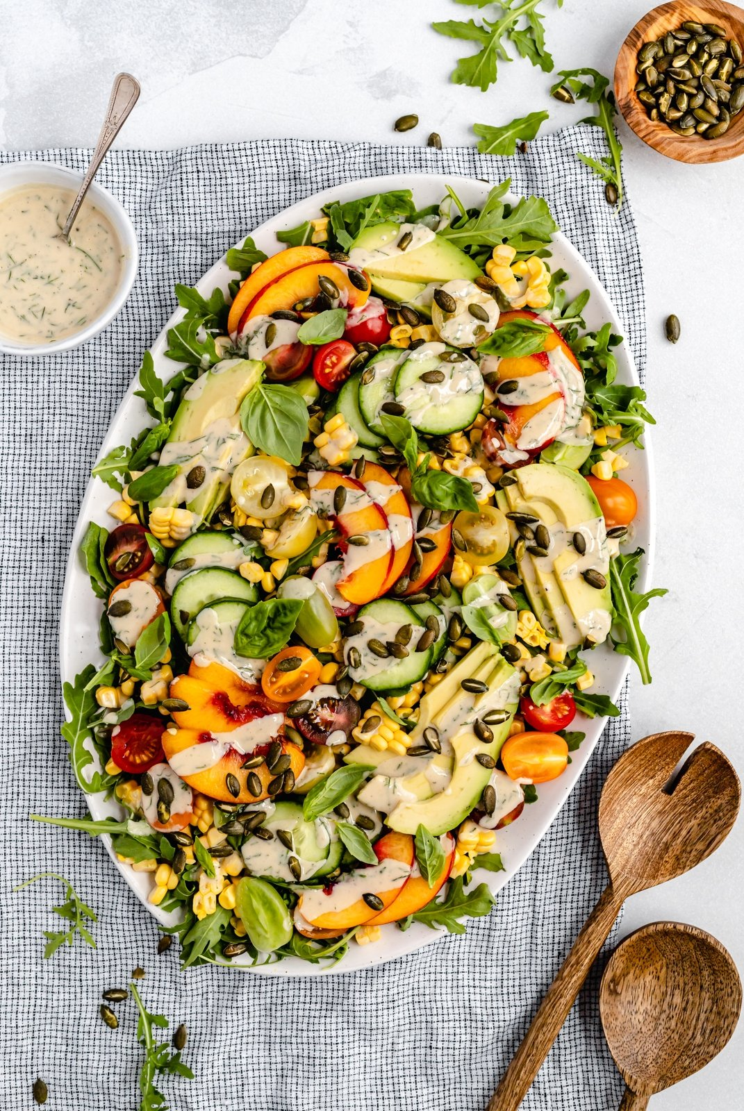 avocado peach tomato salad on a serving platter