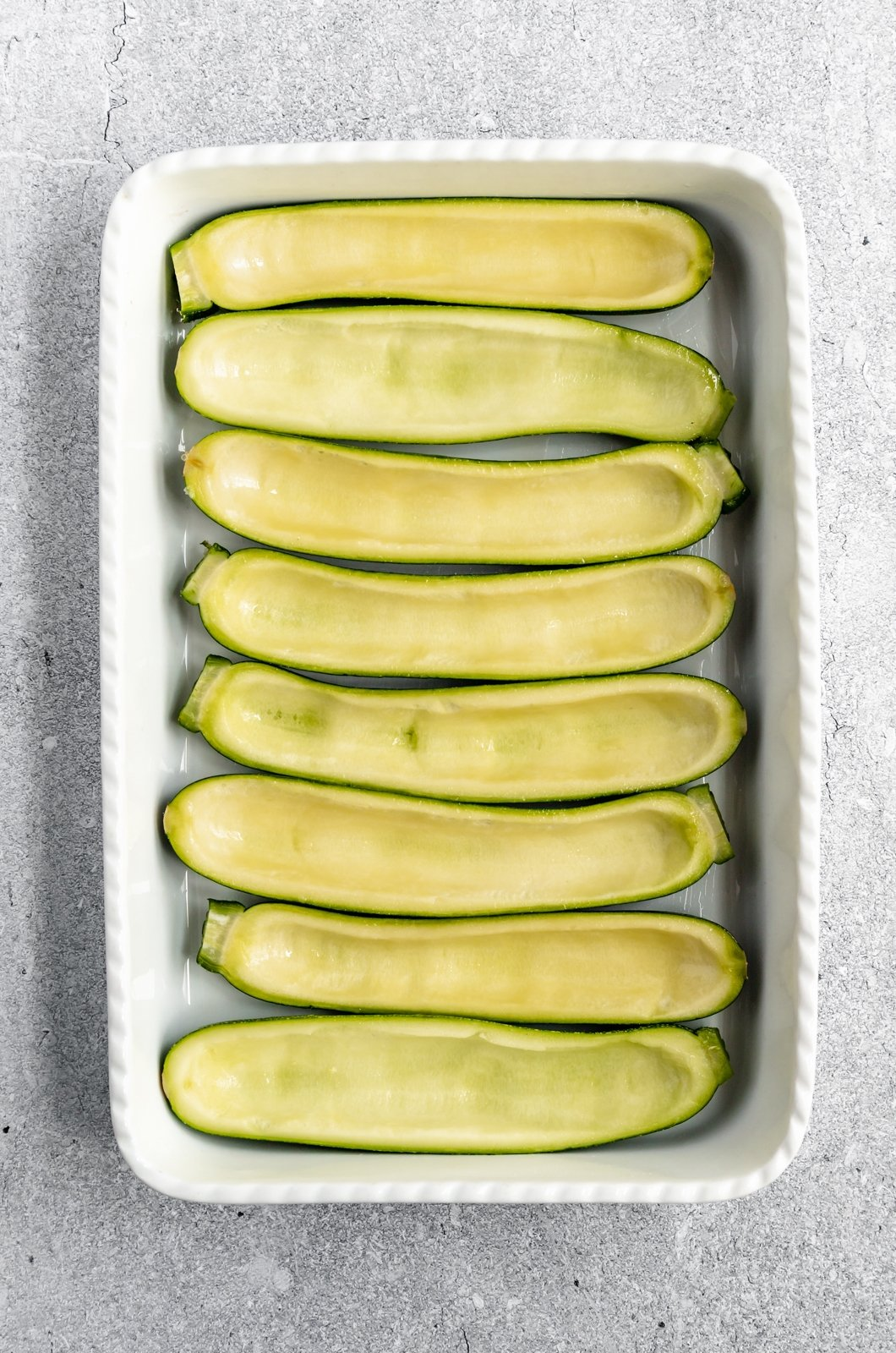 hollowed-out zucchini boats in a baking dish