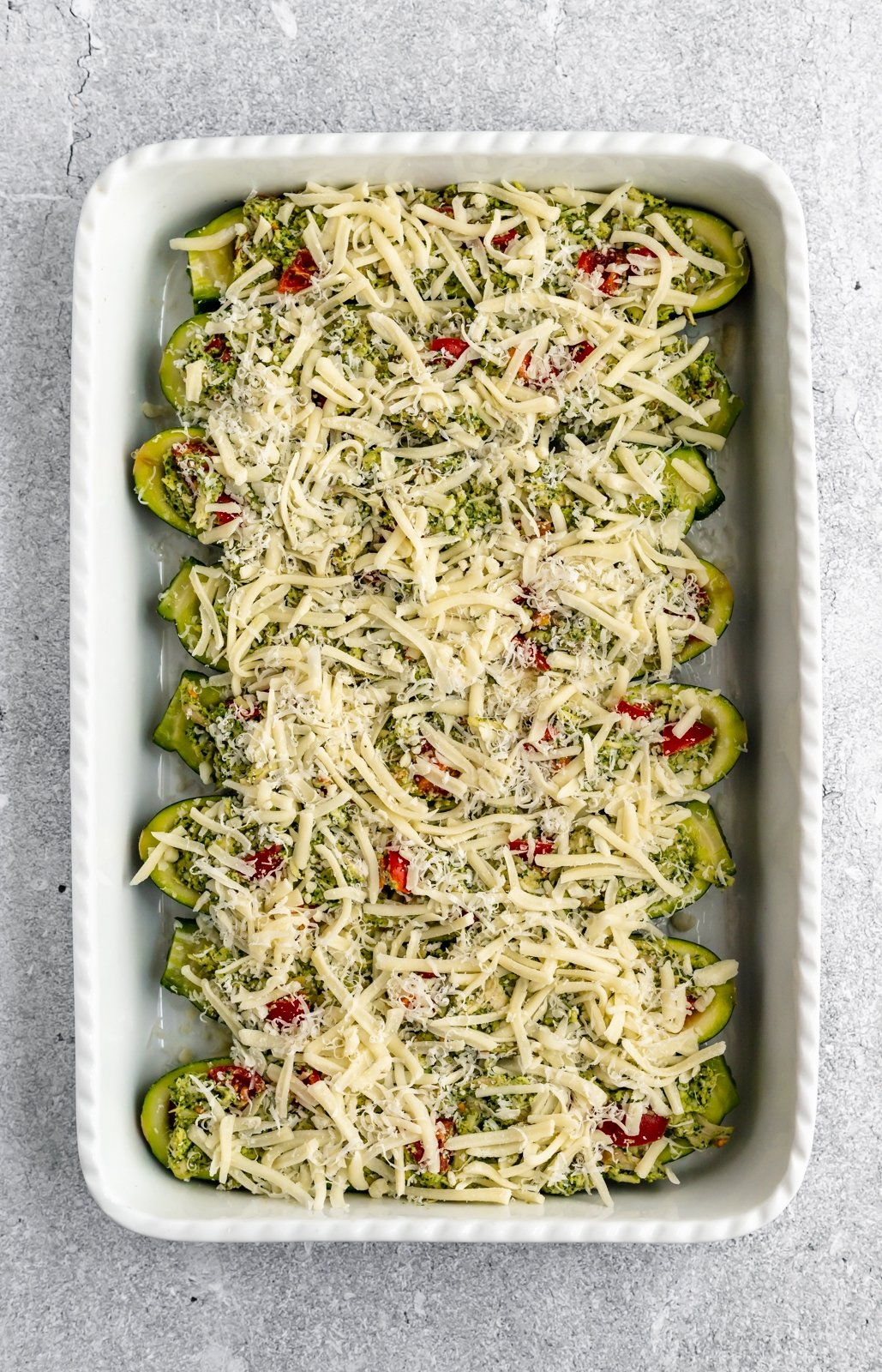 easy pesto chicken zucchini boats unbaked in a baking dish