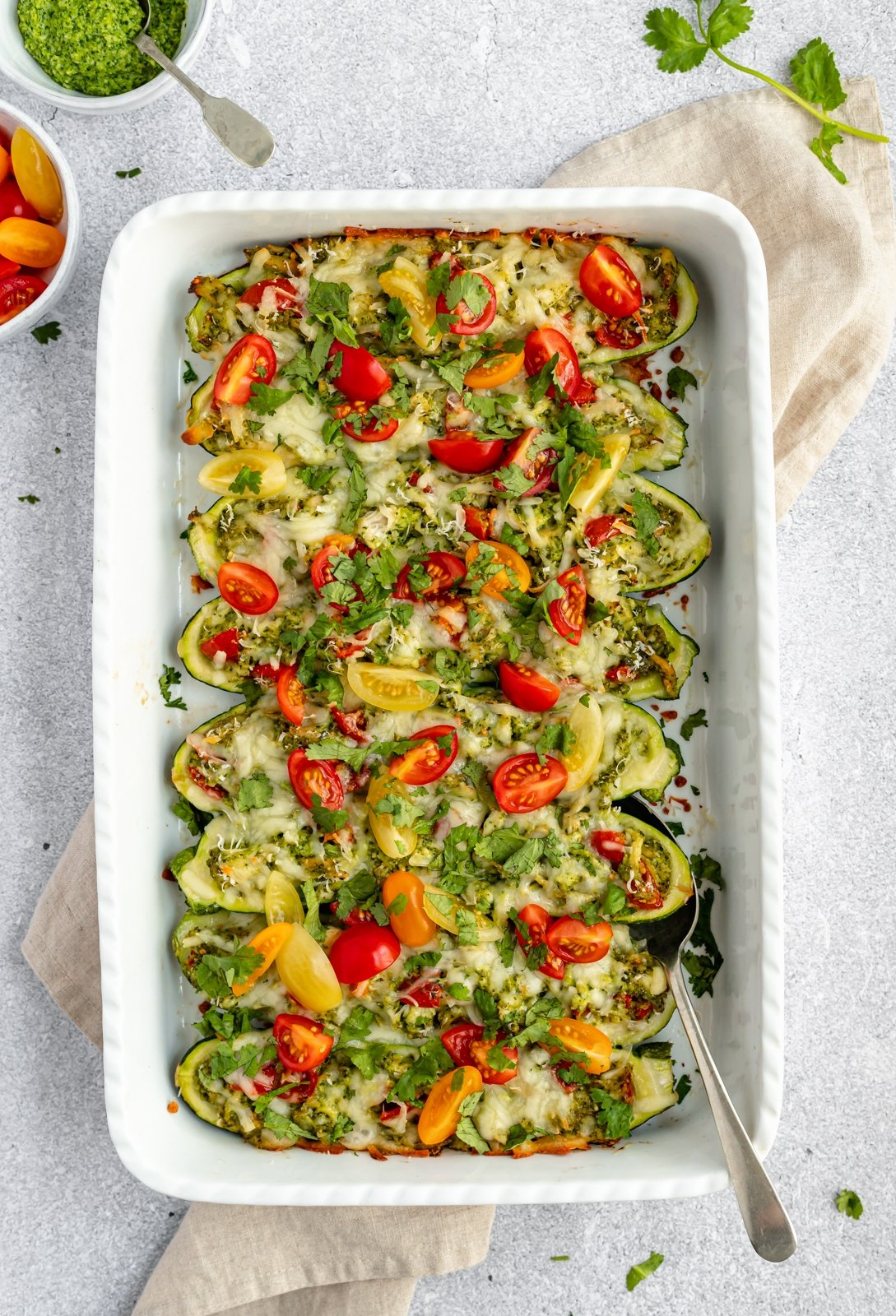 low carb pesto chicken stuffed zucchini boats in a baking dish