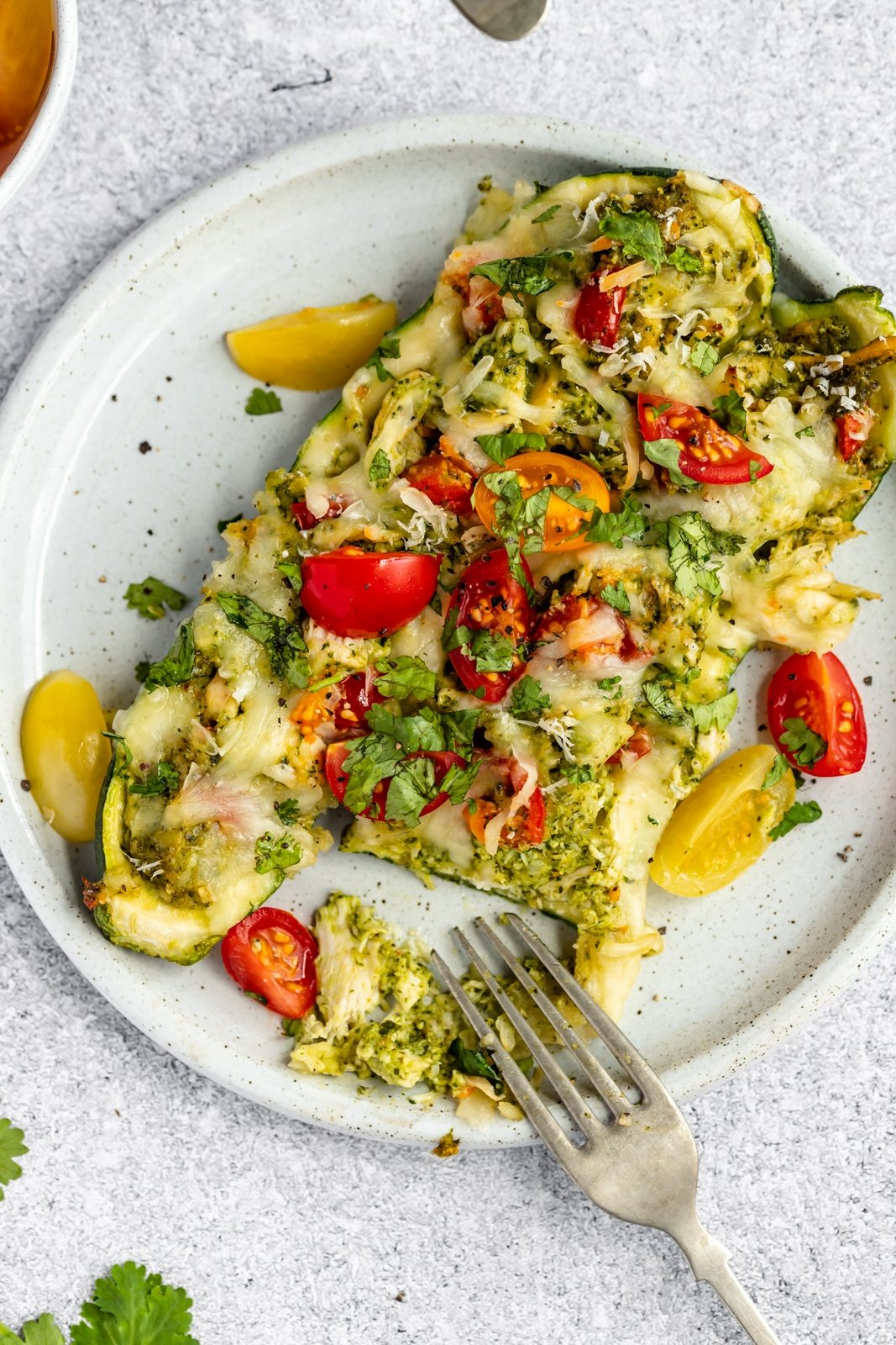easy pesto chicken stuffed zucchini boats on a plate