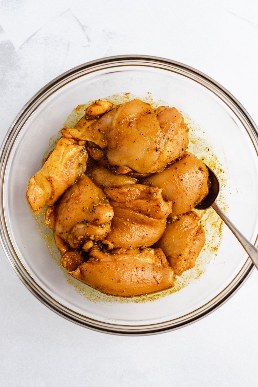 chicken thighs in a bowl of sazon seasoning