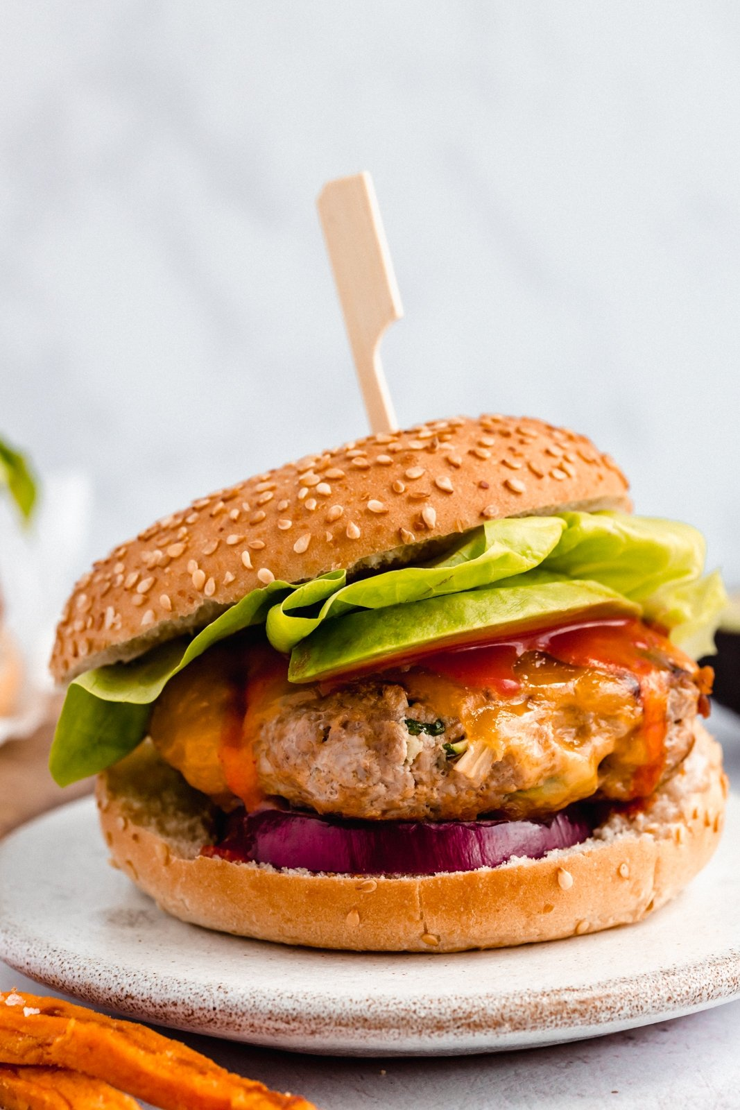 healthy buffalo chicken burger topped with lettuce on a plate