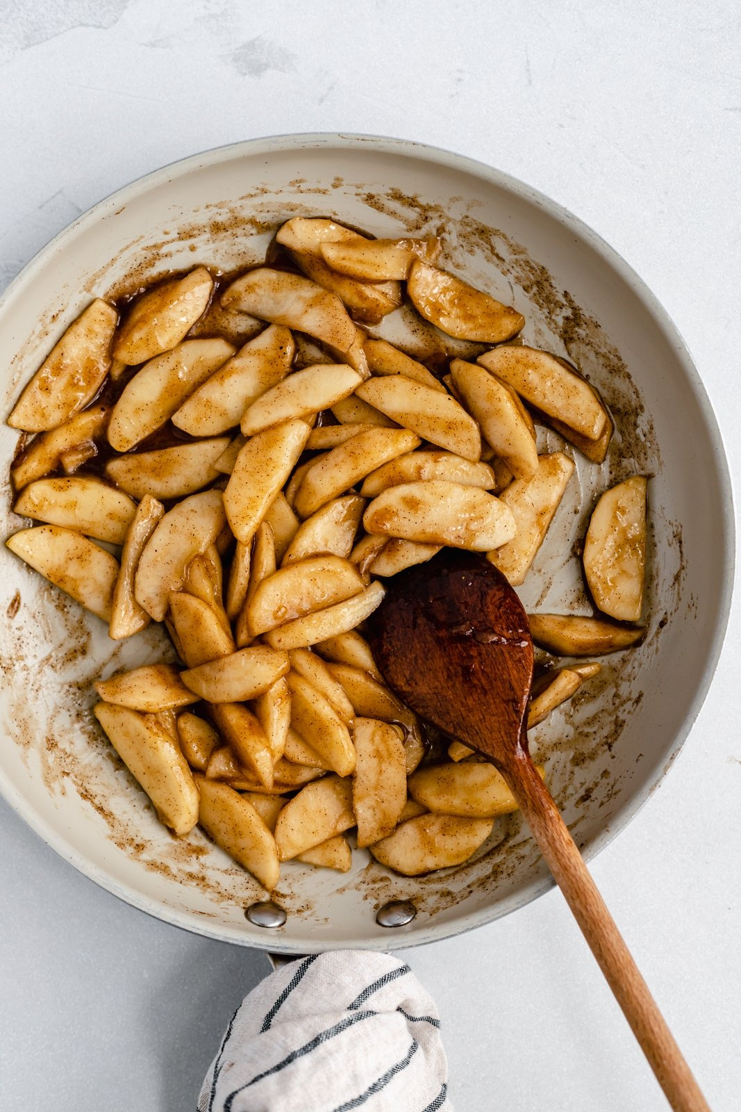 stirring apples in a pan for healthy apple pie bars