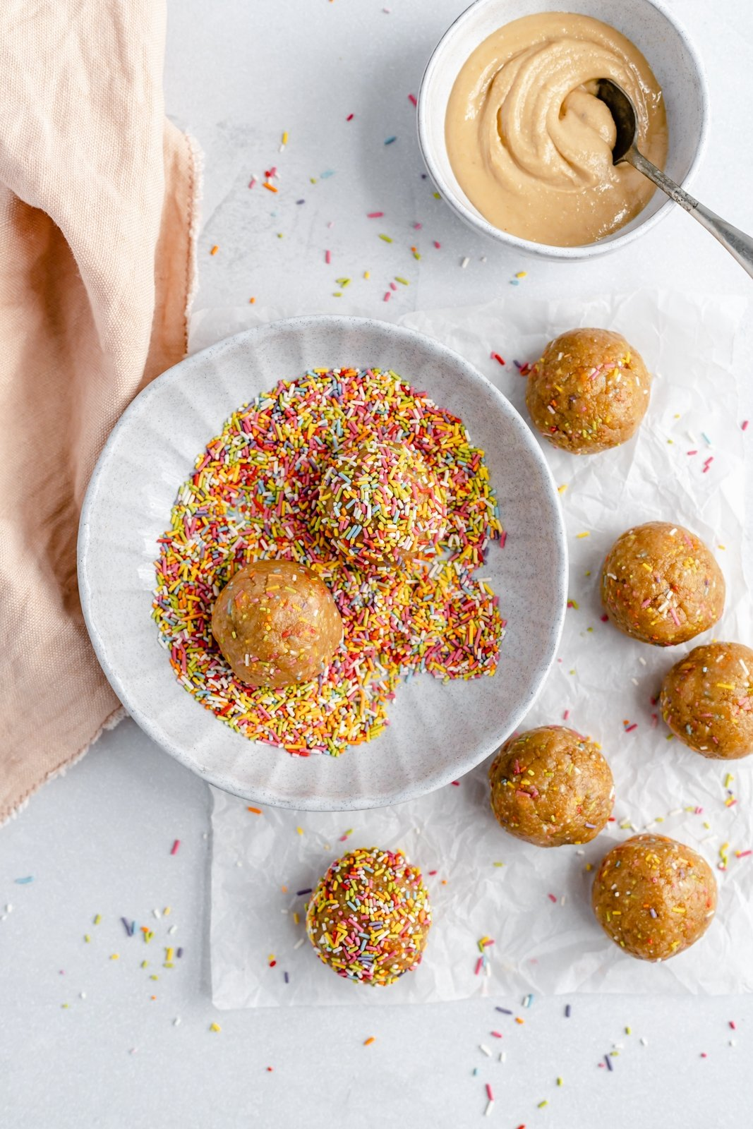 rolling healthy cake batter energy balls in a bowl of sprinkles