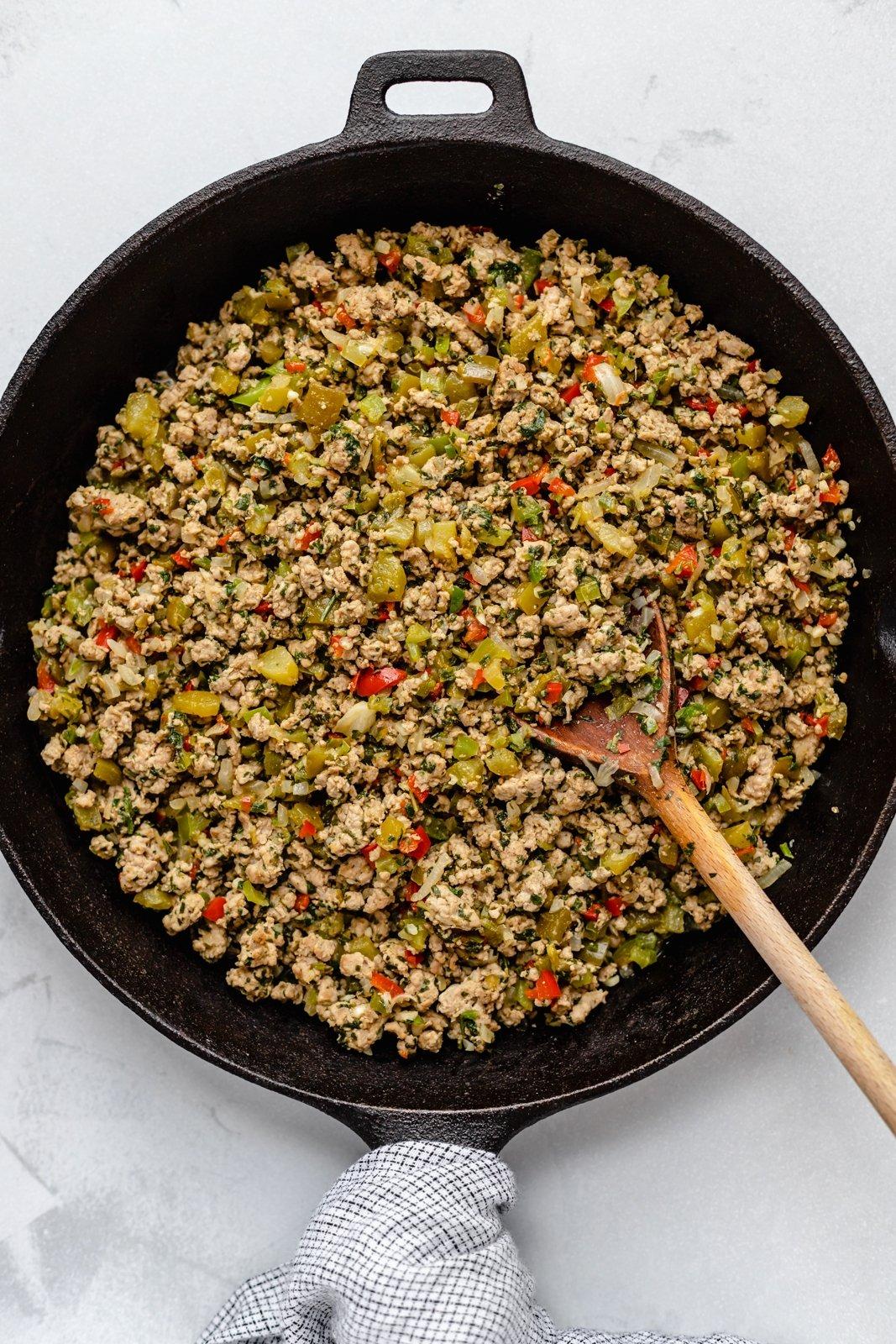 cooking recaito in a pan for green chile chicken burritos
