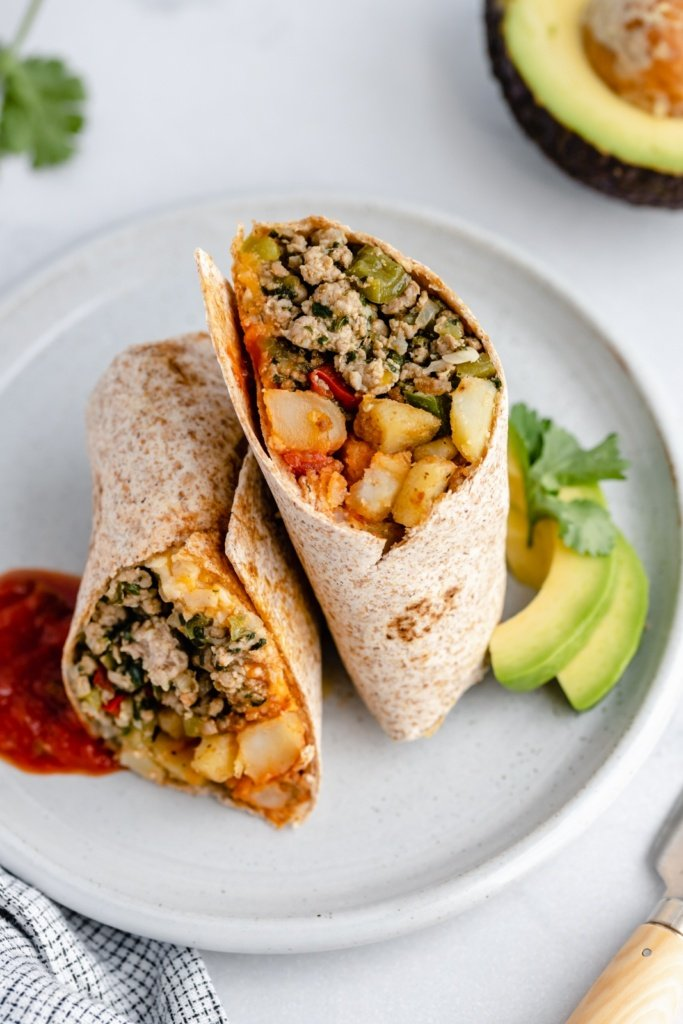 green chile chicken burrito on a plate with avocado