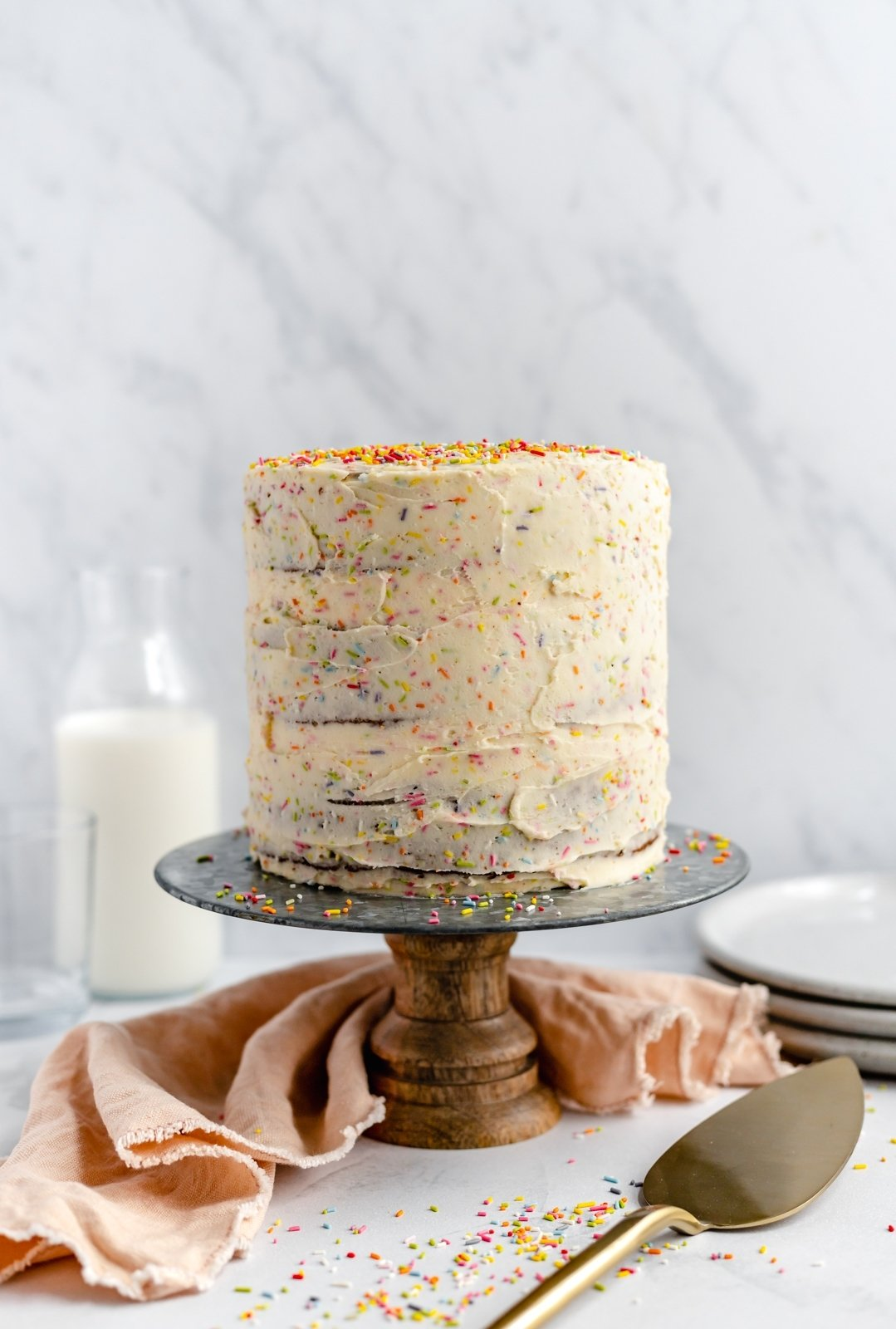 dairy free birthday cake with sprinkles on a cake stand
