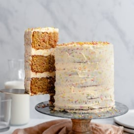 pulling a slice of healthy birthday cake out from a cake stand