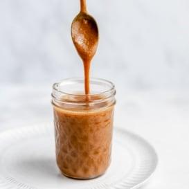 spooning vegan peanut butter caramel sauce out of a jar