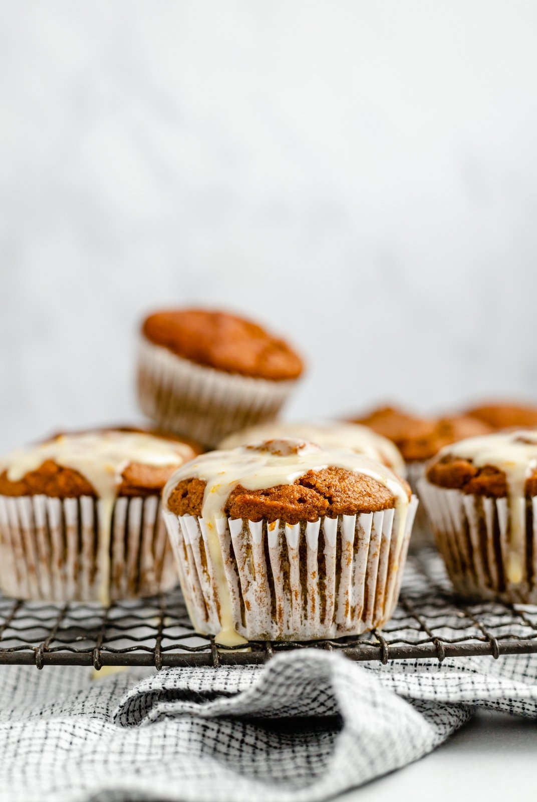 pumpkin orange muffin with orange glaze on a wire rack