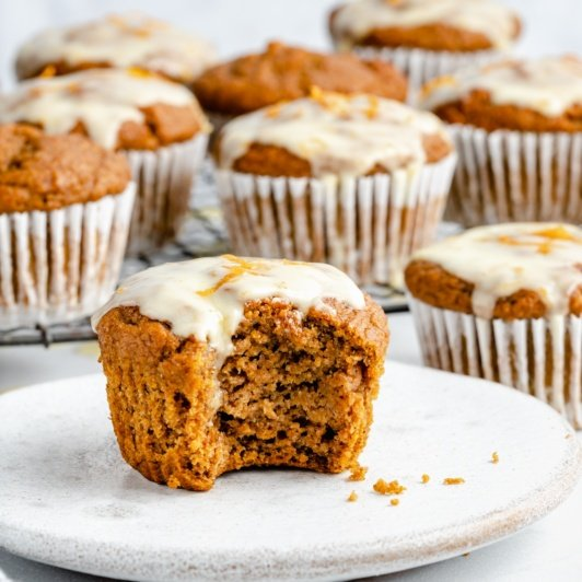 orange pumpkin muffin on a plate with a bite taken out
