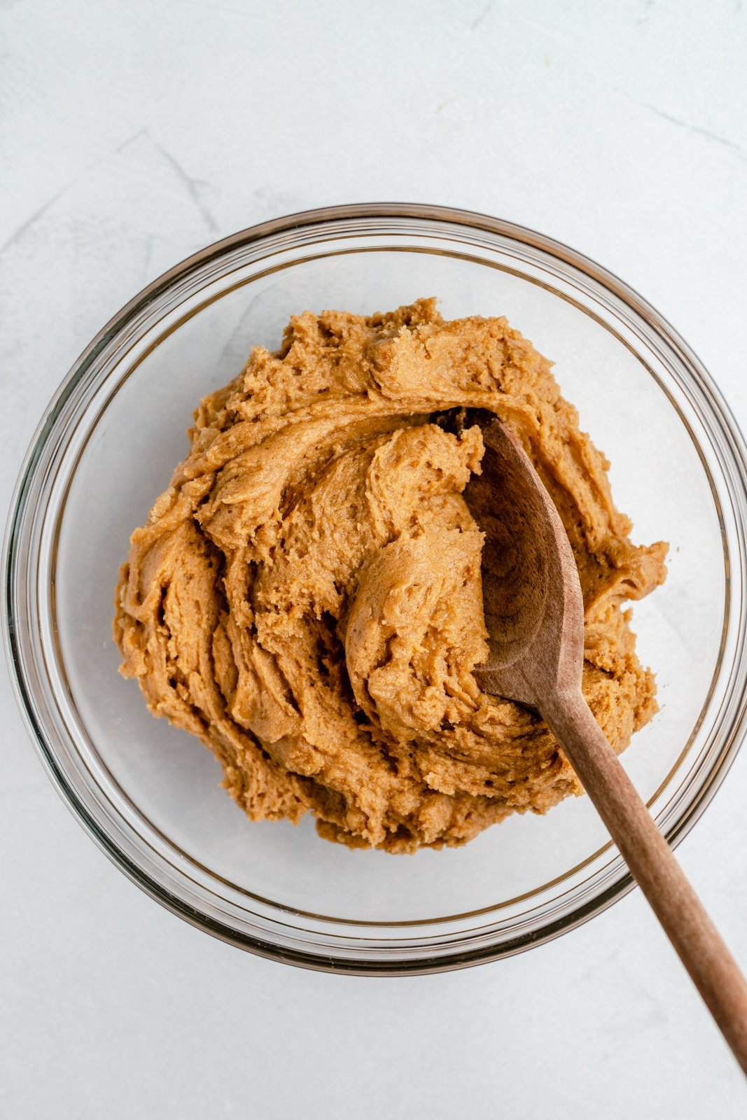pumpkin snickerdoodle dough in a mixing bowl with a wooden spoon