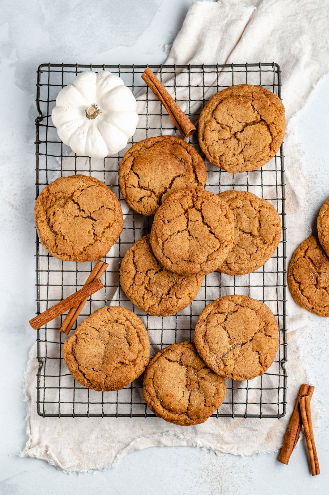 pumpkin snickerdoodles on a wire rack with a white pumpkin