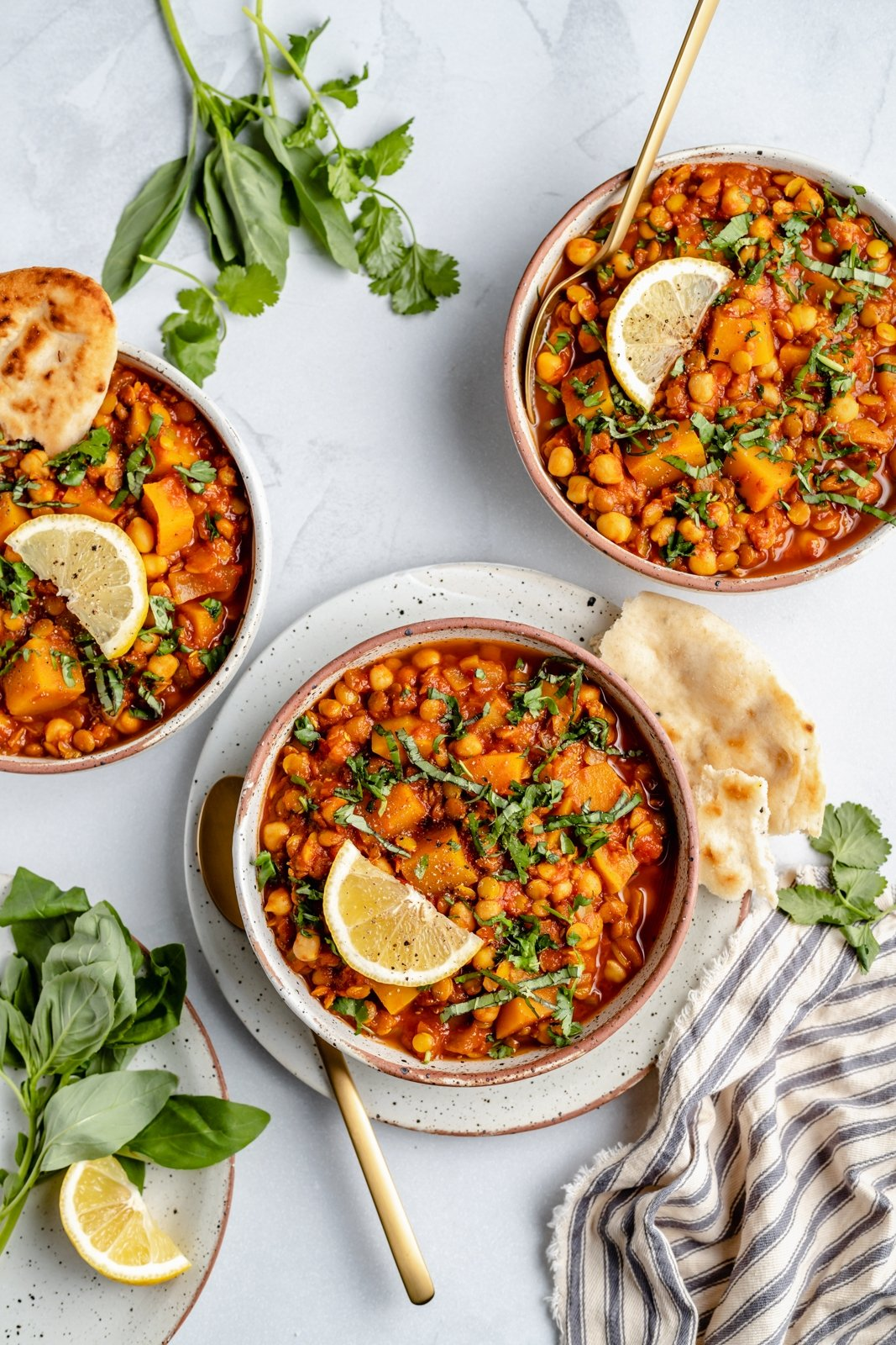vegan Moroccan stew in three bowls with lemon wedges