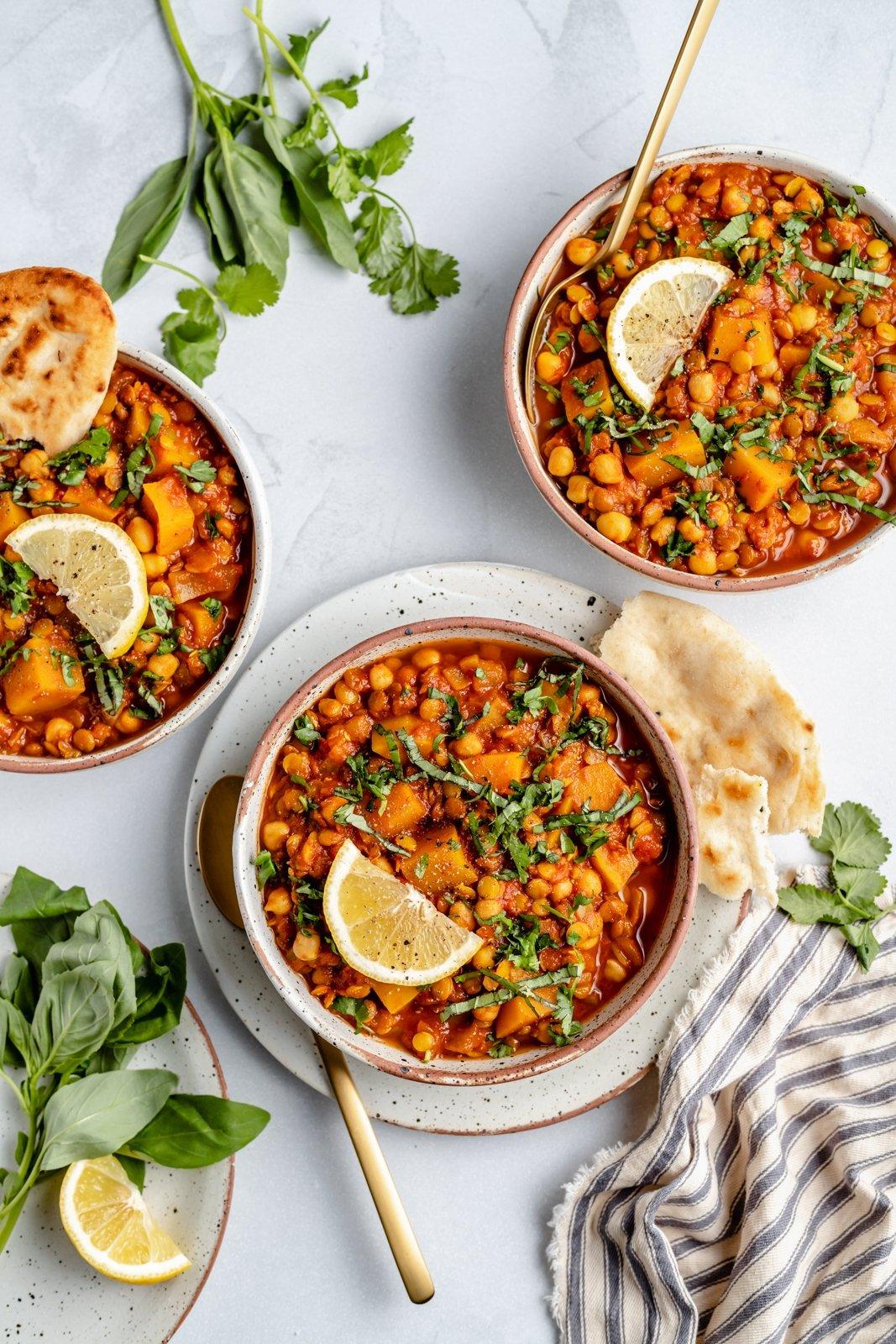 vegan Moroccan stew in three bowls with lemon wedges