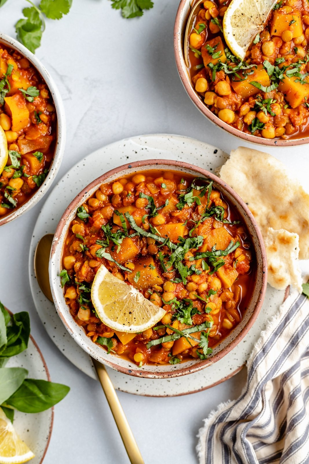 vegan Moroccan stew in a bowl with a lemon wedge