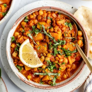 lentil Moroccan stew in a bowl with a lemon wedge