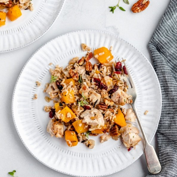 wild rice casserole with butternut squash and chicken on a plate with a fork