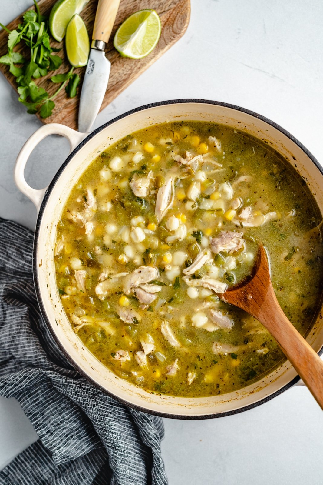 green chicken pozole recipe in a pot with a wooden spoon