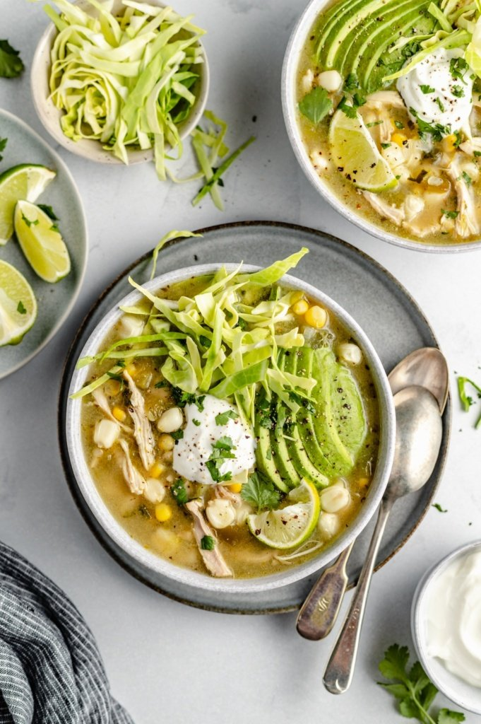 chicken pozole in two bowls topped with avocado, yogurt and cabbage