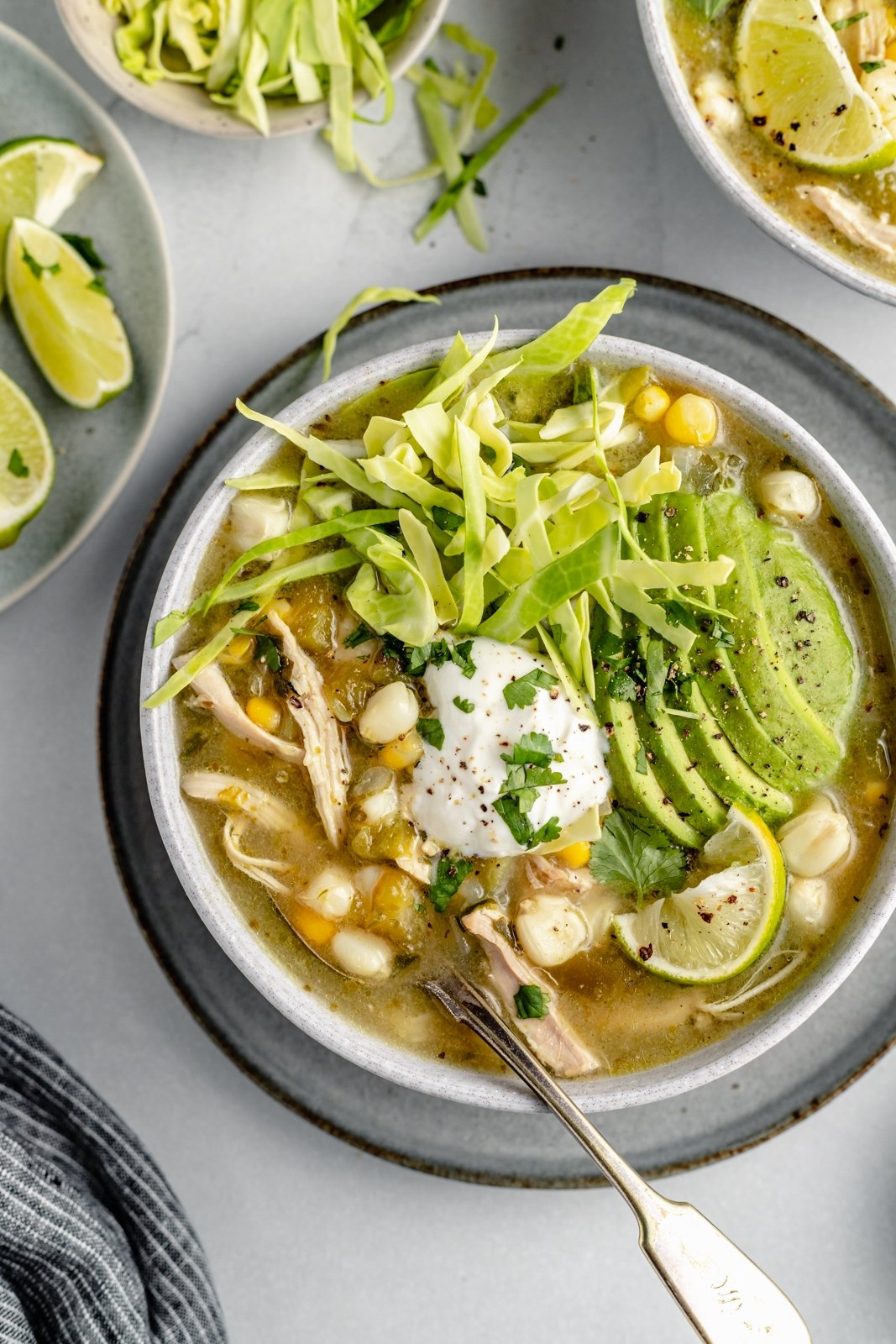 chicken pozole topped with avocado and cabbage in a bowl with a spoon