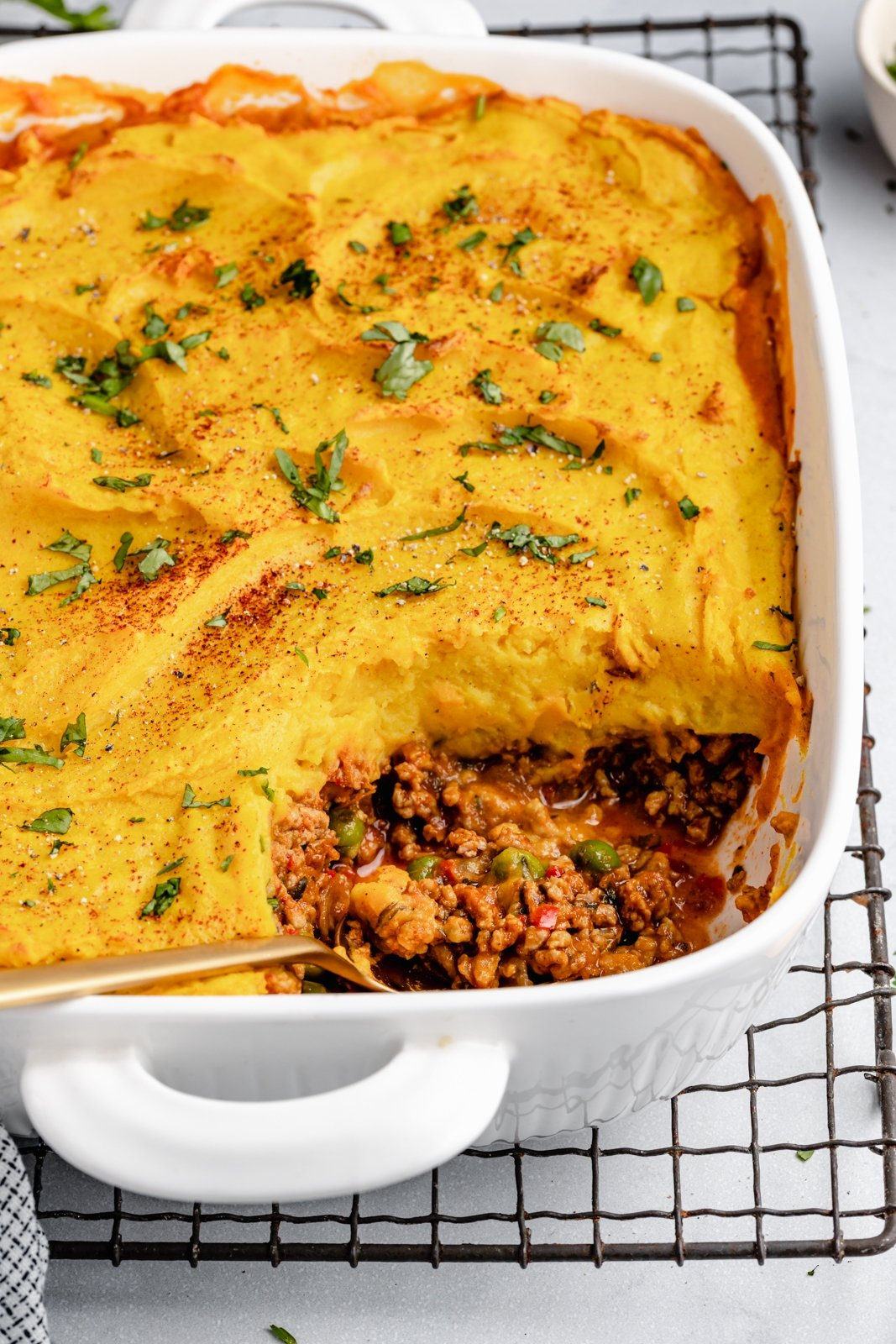 indian shepherd's pie in a baking dish with a spoon