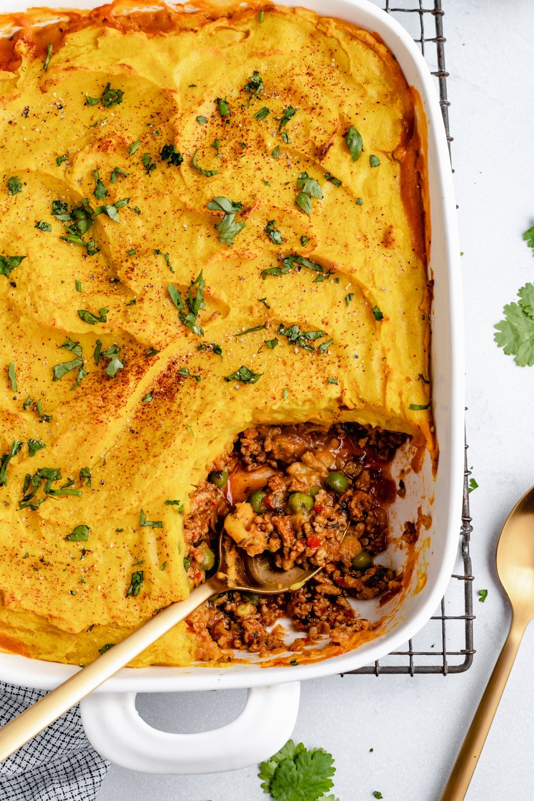 healthy shepherd's pie in a baking dish with a spoon scooping