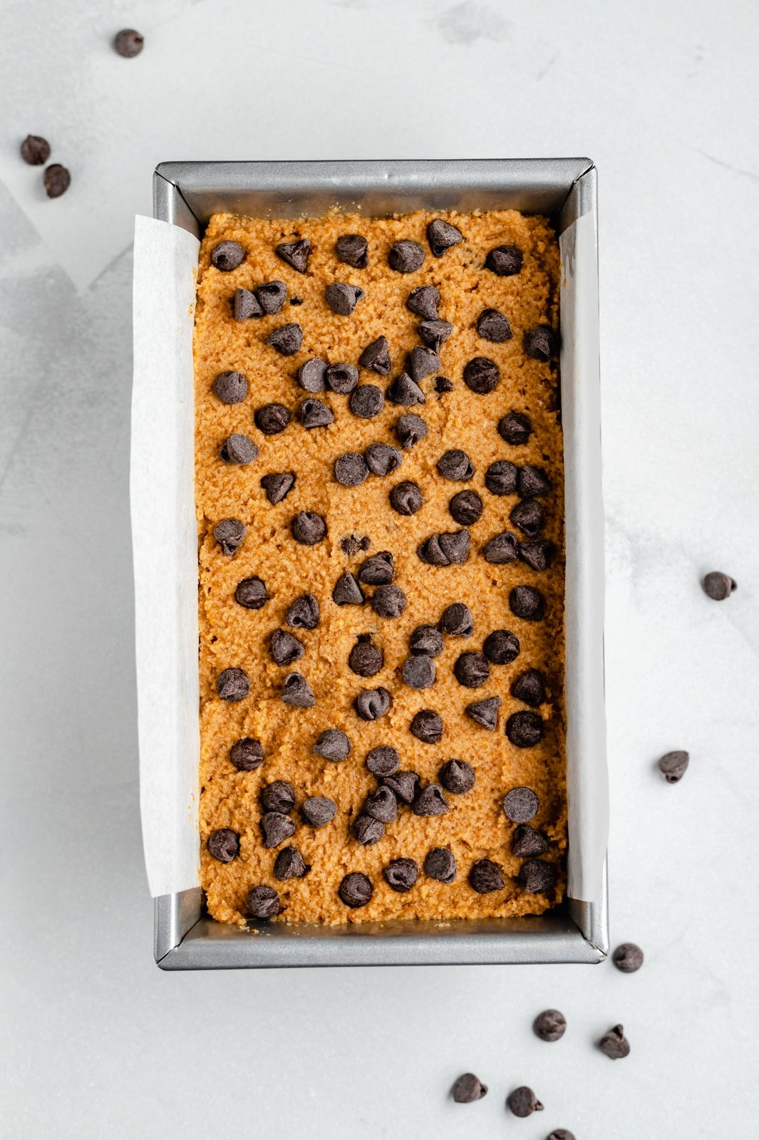 unbaked gluten free pumpkin bread with chocolate chips in a loaf pan
