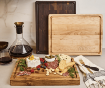 three cutting boards next to a carafe of wine