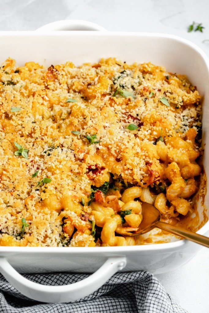 pumpkin mac and cheese in a casserole dish with a spoon