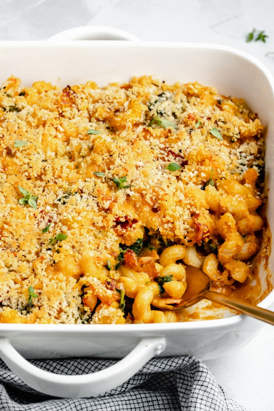 creamy pumpkin mac and cheese bake in a dish with a spoon