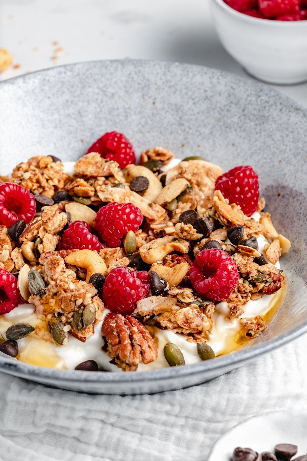 nut and seed granola in a bowl with yogurt and raspberries
