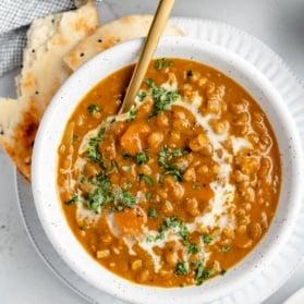 vegan pumpkin lentil soup in a bowl with naan