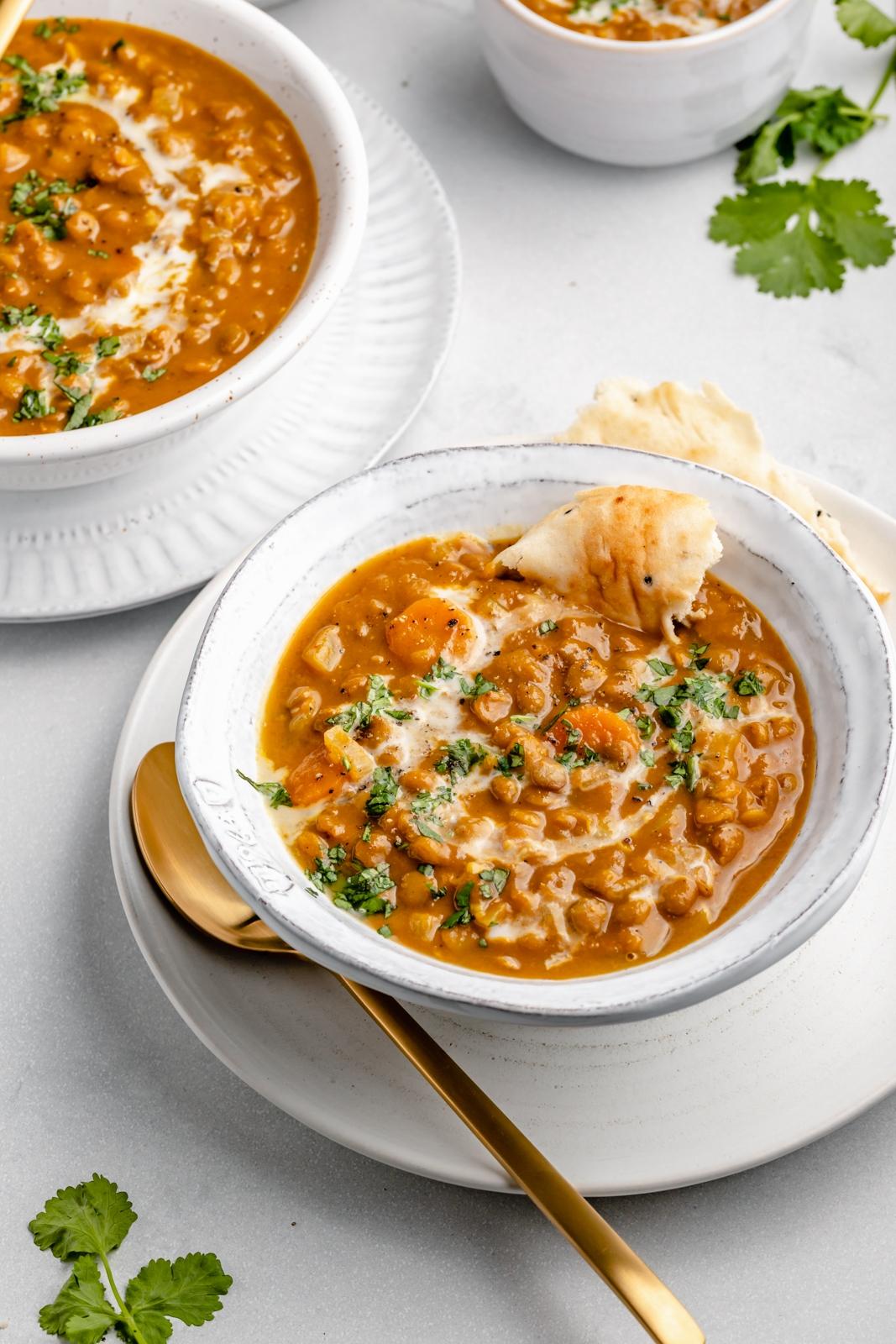 vegan pumpkin lentil soup in a bowl with pita bread