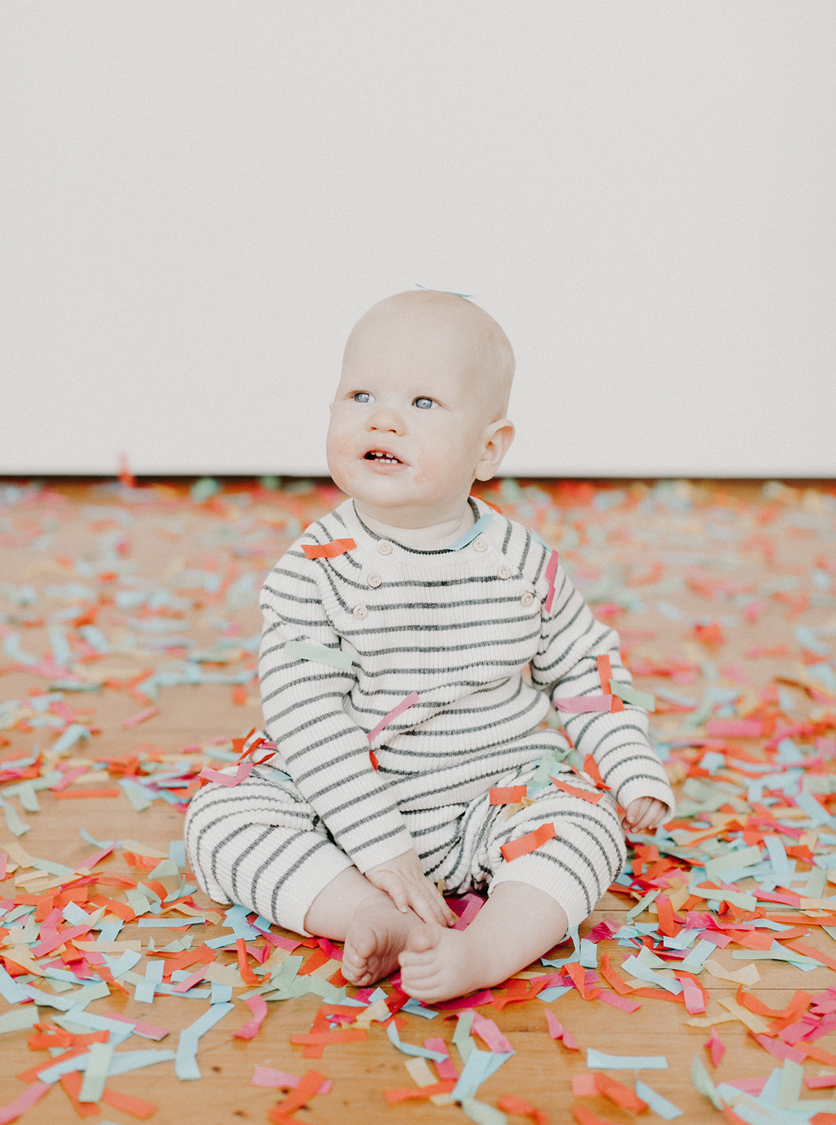 baby sitting in a pile of confetti
