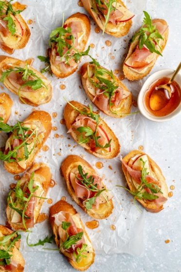 apple and brie crostini with hot honey on parchment paper